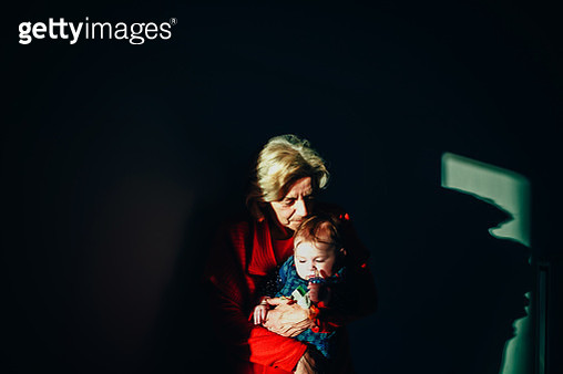 Grandmother Carrying Granddaughter Against Wall At Home - gettyimageskorea