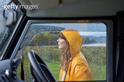 Portrait of woman behind rain covered window - gettyimageskorea