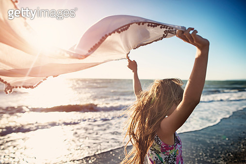 Little girl enjoying sunset on a windy beach. Girl is holding a scarf on wind.    - gettyimageskorea