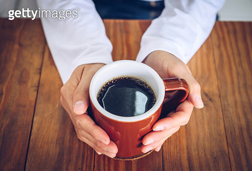 Someone hands holding a mug of black coffee before drinking. - gettyimageskorea