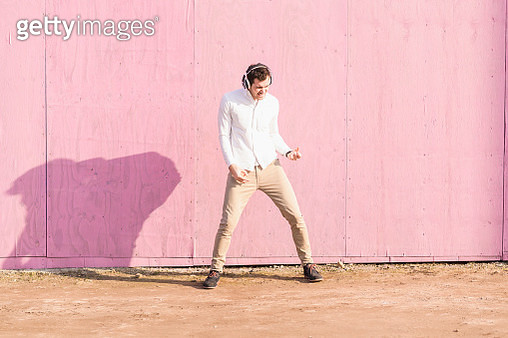 Exuberant young man listening to music in front of pink wall - gettyimageskorea