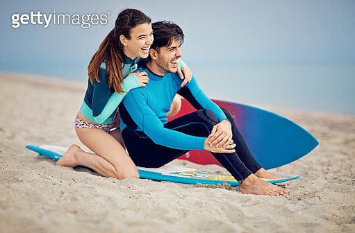 Couple surfers is hugging on the beach and looking the sea - gettyimageskorea