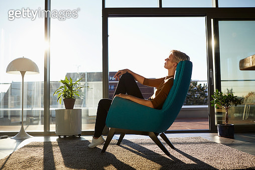 Woman sitting in armchair in sunlight with closed eyes - gettyimageskorea