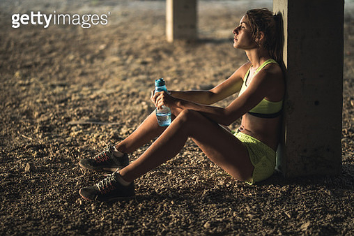 Young female athlete leaning on a pillar while taking a water break from sports training. - gettyimageskorea