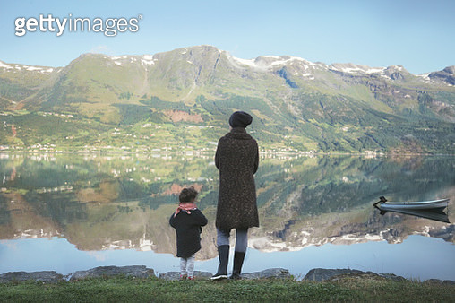 Mother with daughter standing on lakes edge - gettyimageskorea