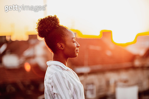 Young African American woman is relaxing on the rooftop - gettyimageskorea