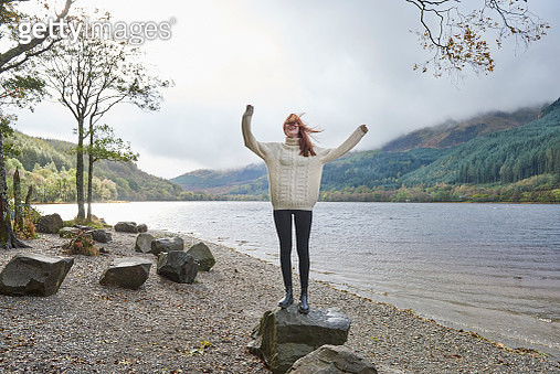 Woman laughing by the side of a loch - gettyimageskorea