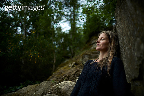 Smiling woman leaning against a rock in nature - gettyimageskorea