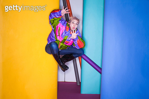 Woman in photo studio, jumping, in mid air, against different coloured rolls of paper - gettyimageskorea