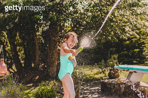 little girl  plays water gun fight at poolside in summer - gettyimageskorea