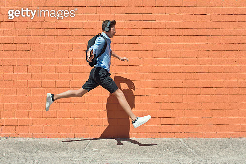 Happy Teen boy by red brick with backpack and headphone jumping and running to school - gettyimageskorea