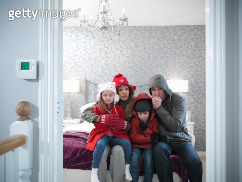 Family wearing winter clothing in bedroom of energy efficient house - gettyimageskorea