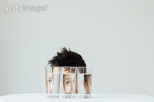Portrait of a child pulling silly face looking through water filled glasses - gettyimageskorea
