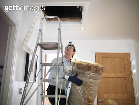 Man preparing to insulate loft in house - gettyimageskorea
