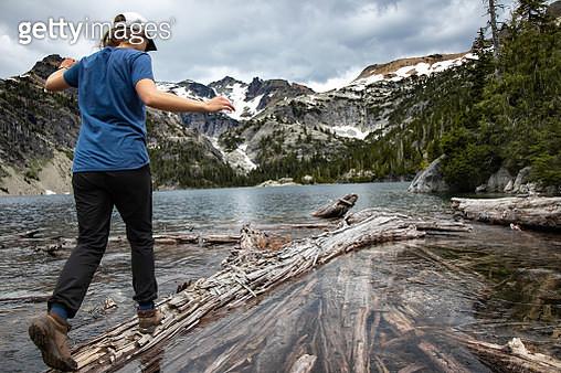 Young hiker girl balances across narrow log on wild mountain lake - gettyimageskorea