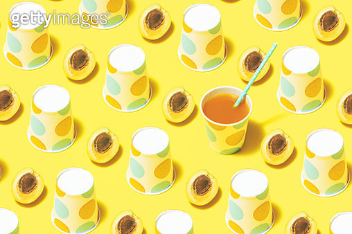 Disposable paper cups on color background. Peach juice and polka dot paper cups flat lay on yellow background. - gettyimageskorea