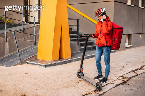 Delivery woman with electric scooter talking on phone - gettyimageskorea