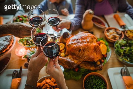 Group of unrecognizable people toasting with wine during Thanksgiving dinner at dining table. - gettyimageskorea