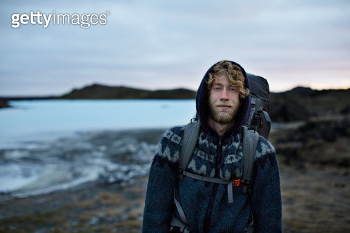 Portrait of cool backpacker smiling confident - gettyimageskorea