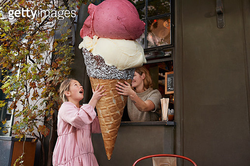Girl buying large ice cream cone from take out counter of cafe - gettyimageskorea