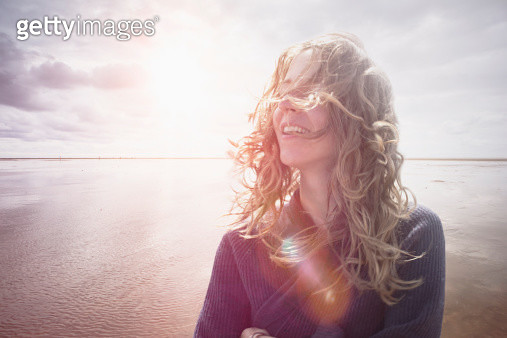 Woman with wind in hair, backlight lens flair - gettyimageskorea
