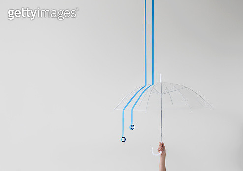 Womans Hand holding umbrella with conceptual rain - gettyimageskorea