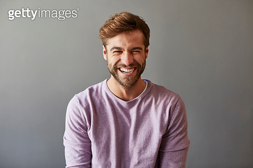 Male professional laughing over gray background. Cheerful businessman is wearing purple t-shirt. - gettyimageskorea