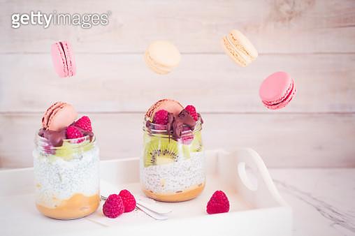 Yogurt cups with toffee, chia, kiwi fruit, raspberries, macarons and chocolate - gettyimageskorea