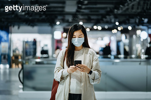 Young Asian woman with surgical face mask using smartphone while shopping in a shopping mall - gettyimageskorea