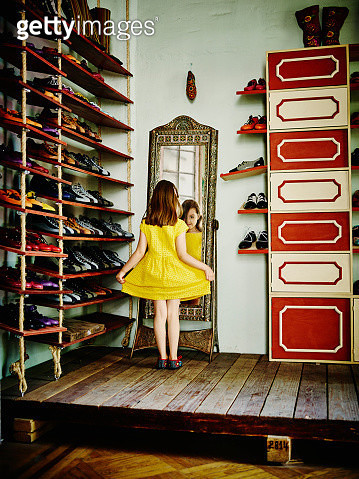 Young girl looking at herself in mirror while trying on shoes in shoe store - gettyimageskorea