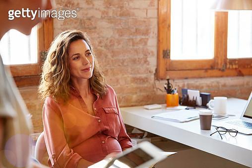 Pregnant businesswoman looking away at desk - gettyimageskorea