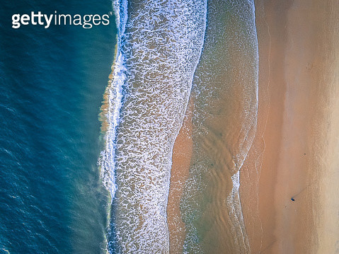 Aerial view of coastline with ocean waves washing down the sand beach at sunrise, Sanya, Hainan, China. Taken by drone from straight above. - gettyimageskorea
