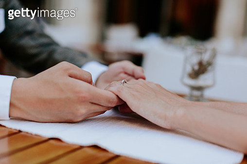 Cropped Image Of Couple Holding Hands At Table - gettyimageskorea