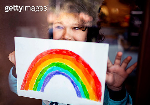 Little boy sticking his rainbow painting on the window - gettyimageskorea