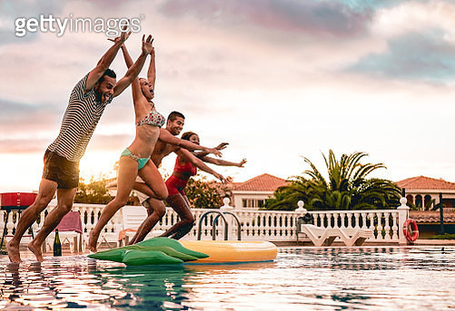 Group Of Happy Friends Jumping In Pool At Sunset Time - gettyimageskorea