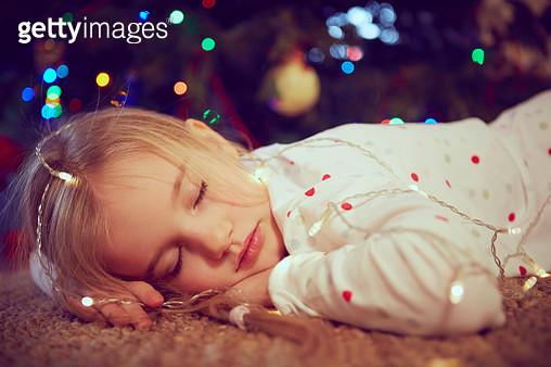 Girl wearing lights asleep on floor at christmas - gettyimageskorea