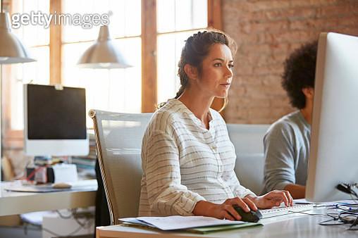 Pregnant businesswoman using computer at desk - gettyimageskorea