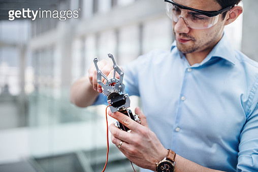 A Young Businessman Or Scientist With Robotic Hand Standing In Office, Working - gettyimageskorea