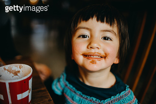 Toddler girl looking at camera with chocolate drink around her mouth - gettyimageskorea