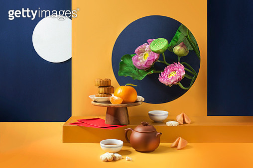 Stack of moon cake and tea set on orange coloured background decorated with Lotus blossom plant. - gettyimageskorea