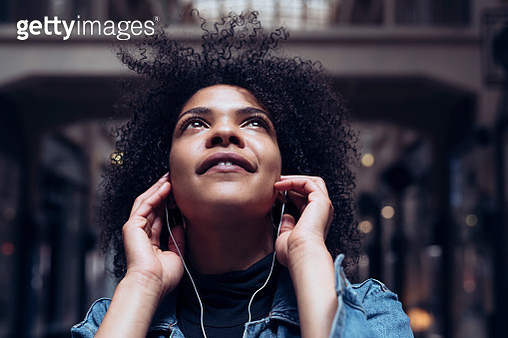 An attractive young woman with African American roots listens to music with headphones. She looks up dreamily and smiles slightly - gettyimageskorea