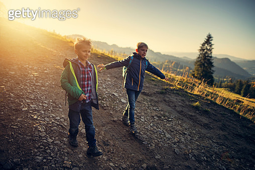 Two little brothers hiking in mountains - gettyimageskorea