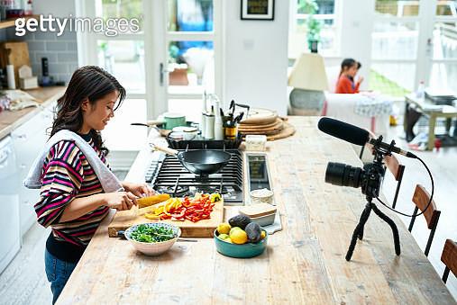 Woman preparing fresh healthy ingredients on work surface, chopping vegetables, talking to video camera, making online vlog - gettyimageskorea