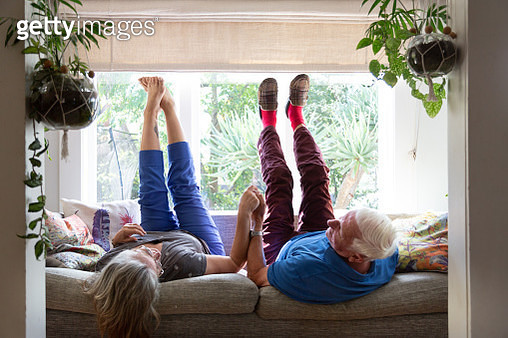 A senior couple lie on the sofa with their legs in the air - gettyimageskorea