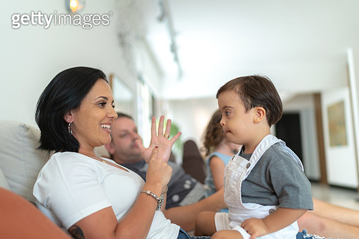 Mother gesturing / education with her Down Syndrome Son at home - gettyimageskorea