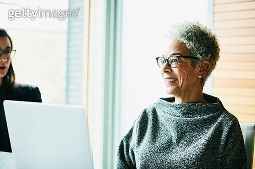 Portrait of smiling senior businesswoman in meeting in office conference room - gettyimageskorea