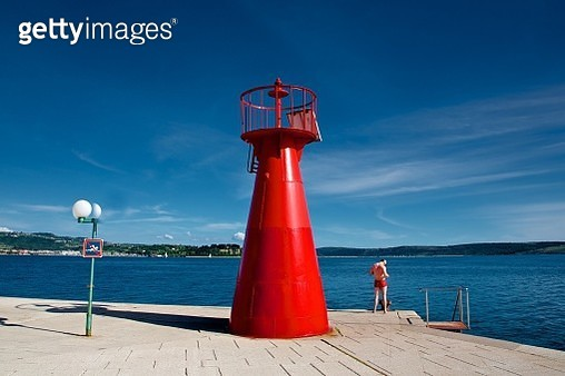 Red lighthouse and guy in red swimwear - gettyimageskorea