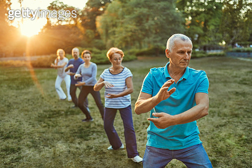 Group of people doing Tai chi in a park - gettyimageskorea