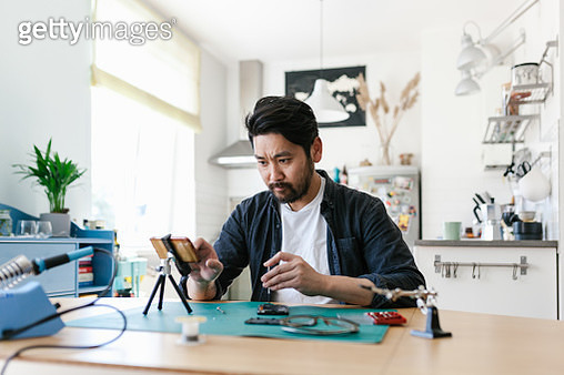 Series of photos of Japanese man learning to repair smart phones and making youtube videos about it. Do it yourself concept. - gettyimageskorea