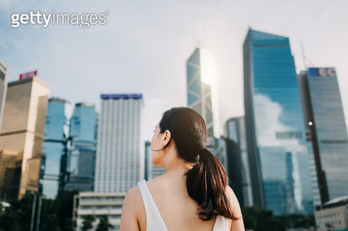Rear view of ambitious businesswoman looking towards the urban financial towers in Central Business District - gettyimageskorea